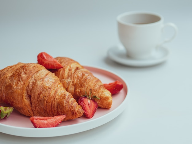 Summer morning with croissants, fresh breakfast with strawberry, and coffee. closeup Premium Photo
