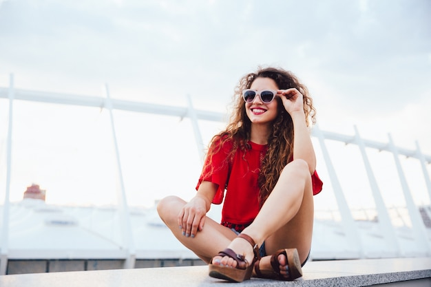 Summer photo of attractive funny girl in sunglasses with curly hair sitting alone Free Photo