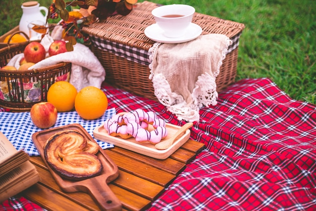 Summer picnic with a basket of food on blanket in the park. Premium Photo