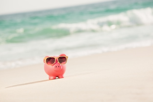 Summer piggy bank with sunglasses on sand 1252 572