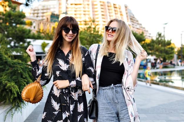 一緒に素晴らしい時間を過ごして、笑顔で路上で時間を楽しむ2つのスタイリッシュなかなり親友の女性の夏の肖像画、エレガントな流行の服を頼むとサングラス、幸せなカップル、関係。 無料写真