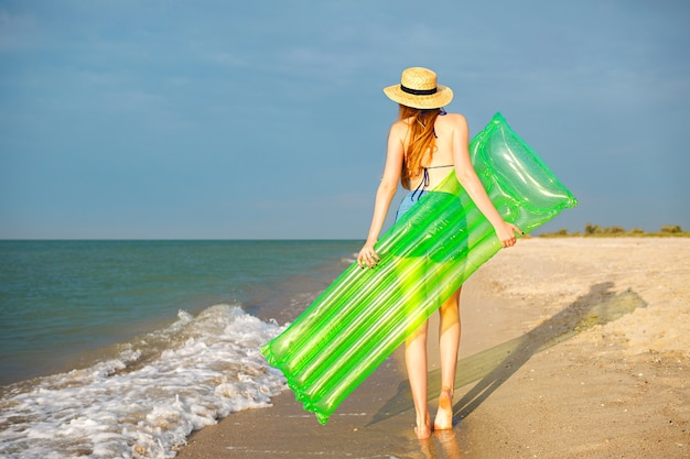 Summer portrait of young woman relaxing on beach, holding big neon air mattress, ready for sea fun, vacation relax mood. Free Photo