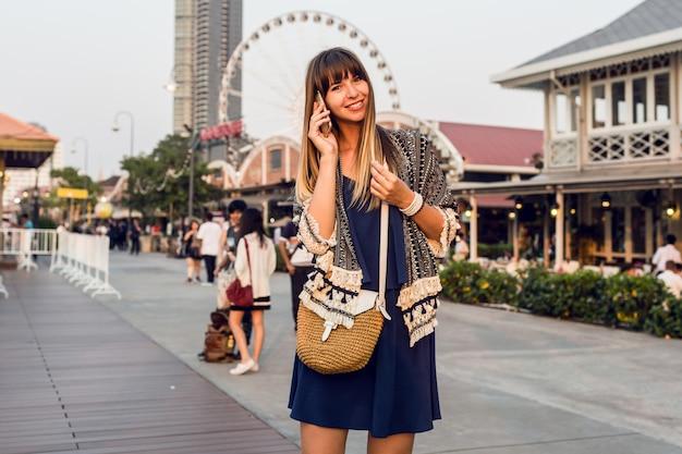Летний позитивный портрет веселой женщины в стильном наряде, говорящей по мобильному телефону и улыбающейся на набережной в бангкоке Бесплатные Фотографии