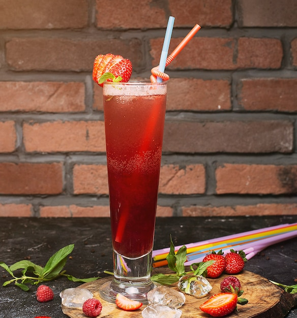 Summer refreshing healthy drink , strawberry smoothie or fresh with mint on a wooden , dark, brick Free Photo