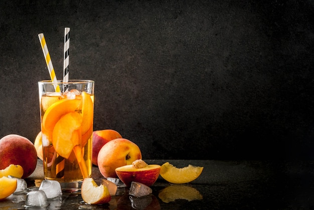 Summer refreshment drinks. iced tea with pieces of organic homemade peach of nectarine. on a black stone background, with ice and ingredients. copyspace Premium Photo