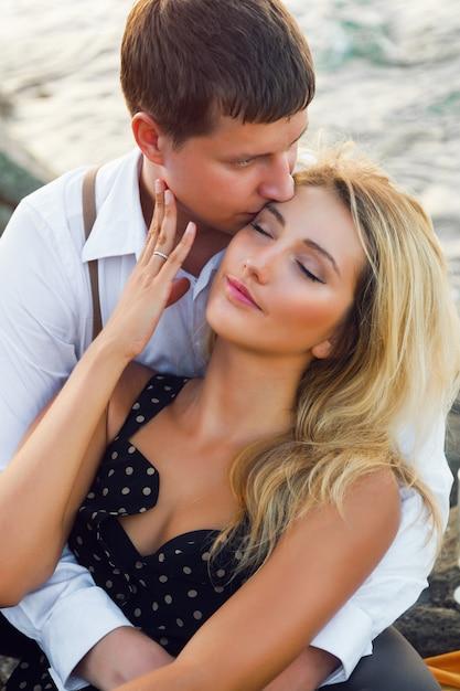 Summer romantic portrait of cute couple hugs near sea Free Photo