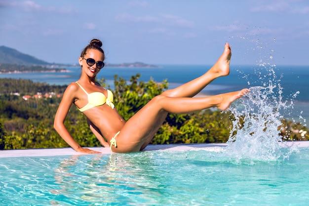 Летняя съемка счастливой возбужденной жизнерадостной молодой женщины, весело проводящей время и плещущейся руками в пейзажном бассейне виллы, роскошной жизни, путешествии на экзотическом острове. Бесплатные Фотографии