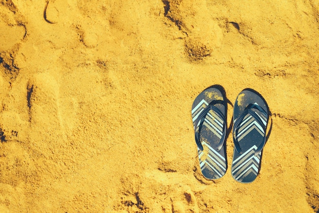Summer slippers. navy blue flip flop on yellow sand beach background. holiday, vacation and travel concept Premium Photo