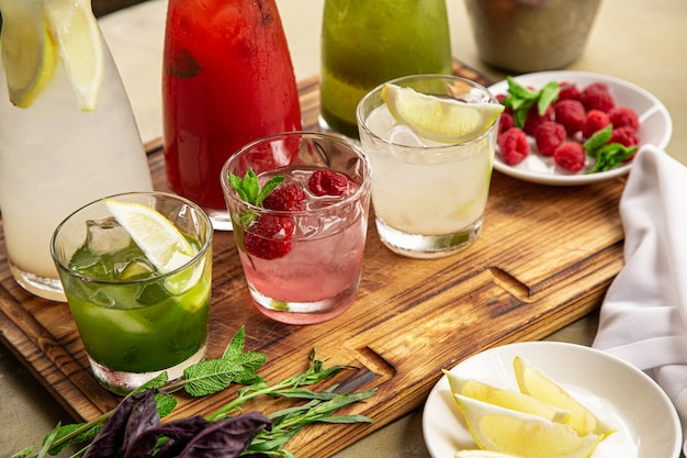 Summer soft drinks, a set of lemonades. lemonades in jugs on the table, the ingredients of which they are made are arranged around. Premium Photo