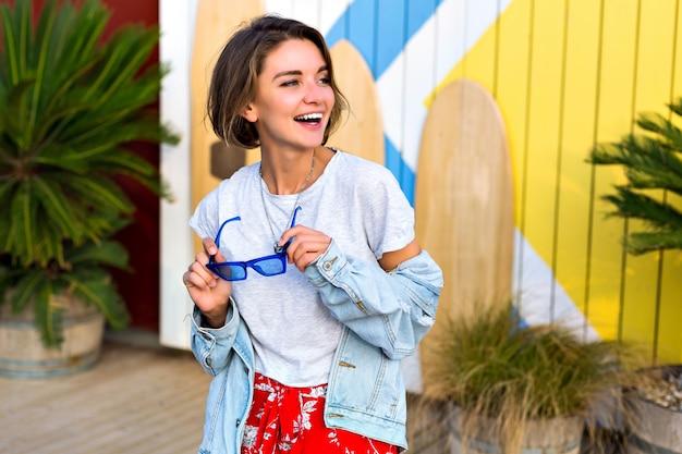 Летняя весна яркий позитивный портрет счастливой улыбающейся брюнетки в модном женственном хипстерском наряде, улыбающейся и веселой, позирующей перед досками для серфинга и пальмами. Бесплатные Фотографии