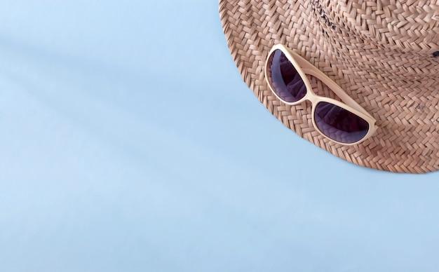 Летняя соломенная шляпа и солнцезащитные очки на голубой поверхности Premium Фотографии