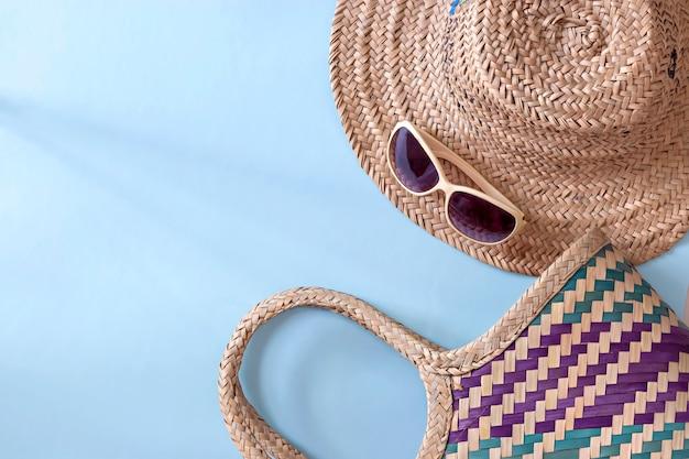 Летняя соломенная шляпа, соломенная сумка и солнцезащитные очки на голубой поверхности Premium Фотографии