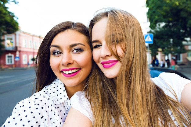 通りで楽しんでいる2人の姉妹の親友ブルネットとブロンドの女の子の夏の日当たりの良い画像、自分撮りを作る、、明るくスタイリッシュな長い髪を作る 無料写真