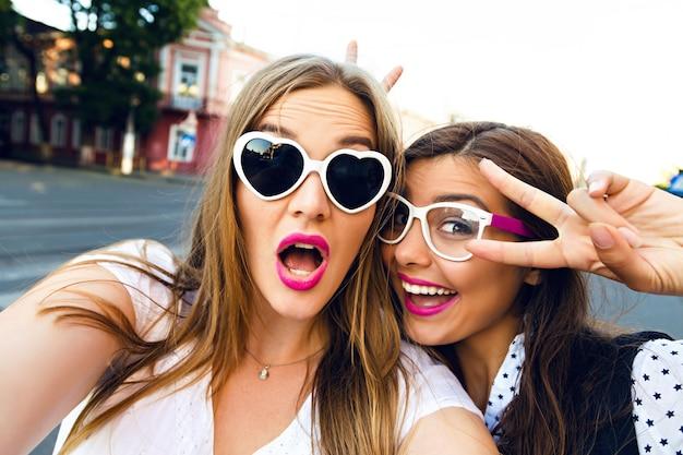 通りで楽しんでいる2人の姉妹の親友ブルネットとブロンドの女の子の夏の日当たりの良い画像、自分撮りを作って、面白いビンテージサングラスをかけて、明るくスタイリッシュな長い髪を作る 無料写真