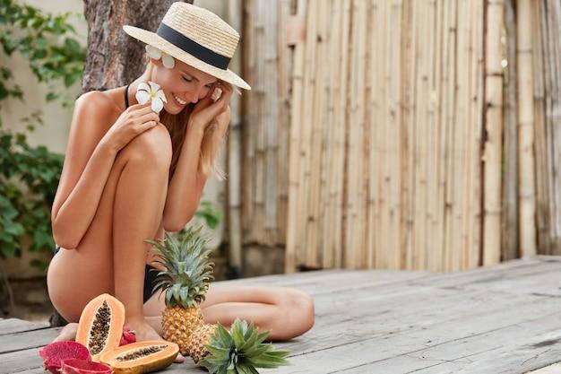夏の時間、健康的なライフスタイル、栄養、食品のコンセプト。甘いパイナップル、パパイヤ、ドラゴンフルーツが好き、サラダを作るつもりの熟したエキゾチックなフルーツに囲まれた麦わら帽子の幸せな素敵な女性 無料写真