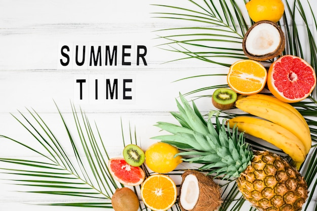 Summer time title among plant leaves near tropical fruits Free Photo