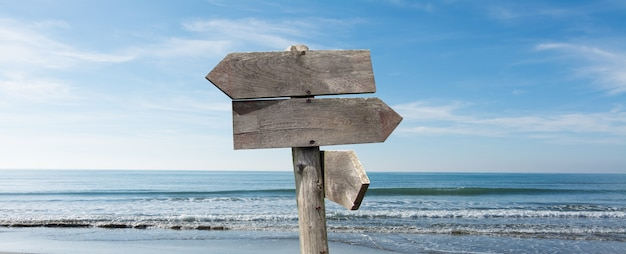 Summer travel destinations options. direction road sign with wooden arrows on beach and sea Premium Photo