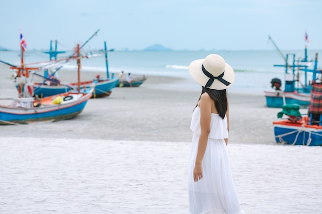 夏の旅行休暇の概念、ドレスと麦わら帽子のホアヒン、タイの海のビーチの上を歩いて幸せな旅行者アジアの女性 Premium写真