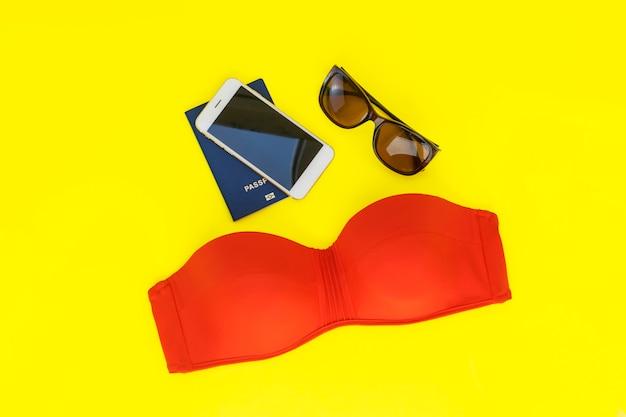 Summer travel vacation  flat lay. hello summer. wanderlust. red swimsuit, glasses, passport on a yellow background Premium Photo