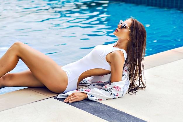 高級ホテルのプールのそばでリラックスした見事な陽気な女性の夏のトレンディな肖像画 無料写真