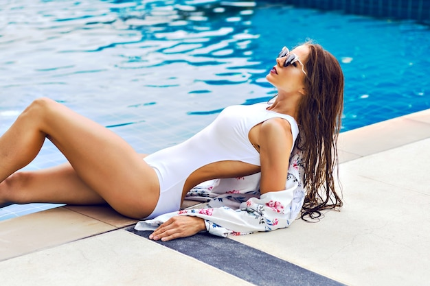 Summer trendy portrait of stunning sportive woman relaxed near pool at luxury hotel Free Photo