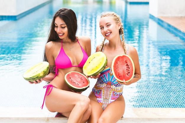 プールの近く楽しんで、おっぱいの近くに2つの大きなスイカを持って、驚いたしかめっ面、クレイジーな感情、明るいビキニの2人のかなり若い女の子の夏のトロピカルポートレートは、休暇をお楽しみください。 無料写真