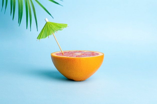 Summer vacation concept. grapefruit with a cocktail umbrella on a colored background. tropics, sun, beach, vitamins, fruits, summer and good mood Premium Photo