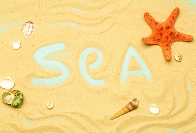夏、海の背景にあるビーチでの休暇。碑文と単語「海」は、日当たりの良い夏の天候でビーチの砂の上に。海、海、リラクゼーションの裏庭。 Premium写真