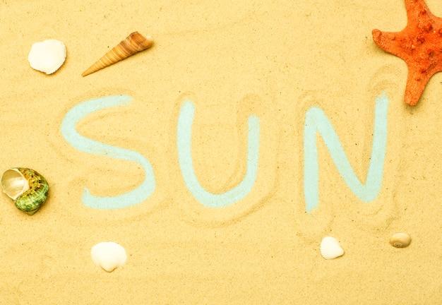 夏、海の背景にあるビーチでの休暇。晴れた夏の天候でビーチの砂の上の碑文と単語「太陽」。海、海、リラクゼーションの裏庭。 Premium写真