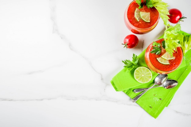 Summer veggie food, cold soup gazpacho in glasses with with fresh celery, parsley and lime juice. white marble background copy space Premium Photo