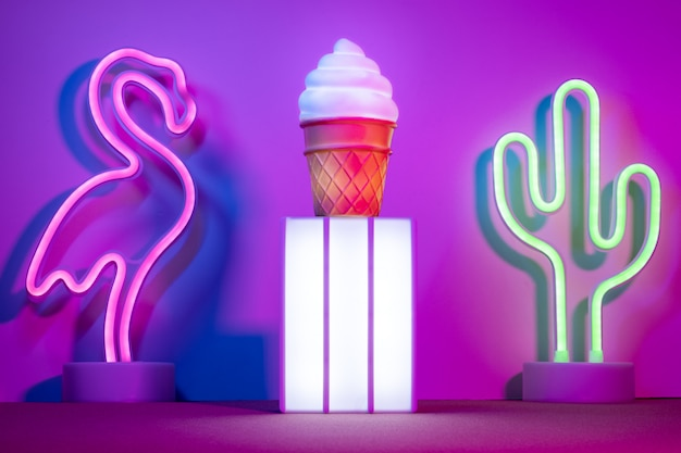 Summer with lightbox and flamingo, cactus and ice cream with neon pink and blue and green light on table Premium Photo