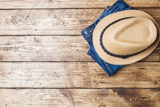 Summer women's clothes. flat lay fashion photo. blue jeans and sun hat on wooden background. copy space Premium Photo