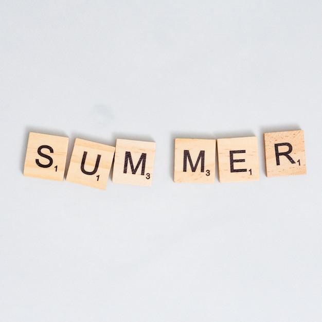 Summer word written on wooden block on gray surface Free Photo