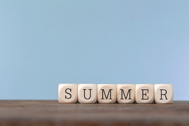 Summer word written in wooden cube on wooden table Premium Photo