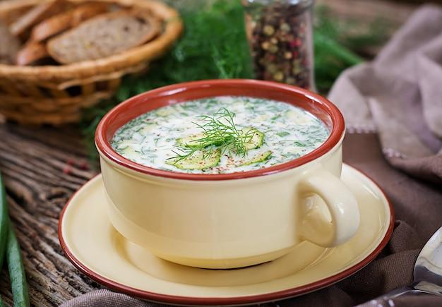 卵、キュウリ、木製のテーブルのディルと夏のヨーグルトの冷たいスープ。オクローシカ。ロシア料理 Premium写真