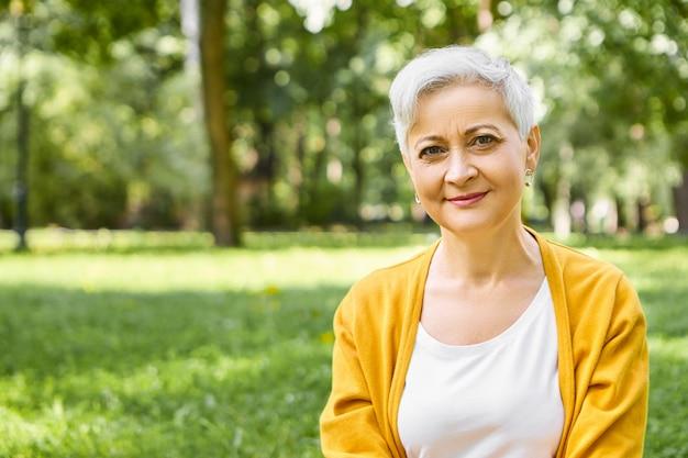 Estate, persone mature, età e concetto di svago. colpo esterno del pensionato alla moda donna caucasica con i capelli corti grigi che indossa cardigan giallo rilassante nella natura selvaggia, con un sorriso Foto Gratuite