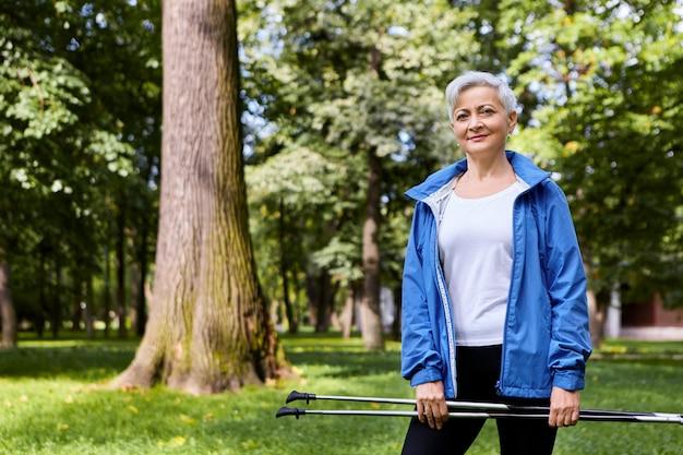 スカンジナビアのウォーキングに行く、両手でスキーストックを持って屋外でトレーニングする美しいスタイリッシュな高齢者の夏のショット。エネルギー、活動、健康、高齢者、スポーツの概念 無料写真