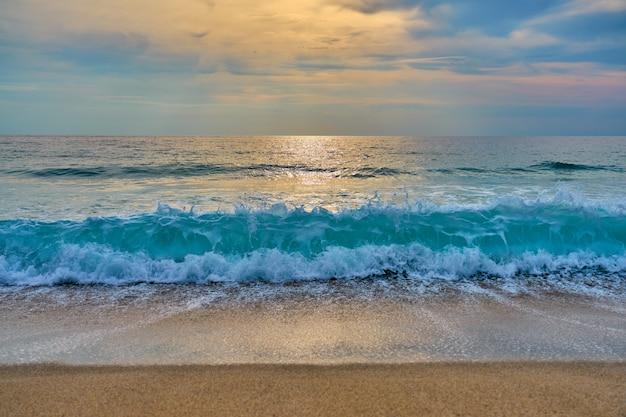雲の後ろの太陽は水と波に反射し、泡が砂にぶつかります。 Premium写真
