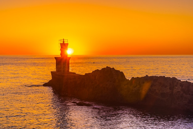 The sun behind the lighthouse at sunset in the town of pasajes san juan. gipuzkoa, basque country Premium Photo