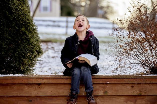 Sole che sorge su un ragazzino carino che legge la bibbia nel mezzo di un parco invernale Foto Gratuite
