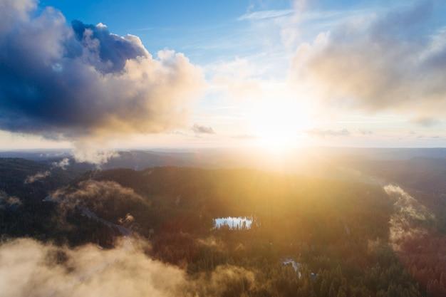 녹지로 덮인 암석 위로 떠오르는 태양 무료 사진