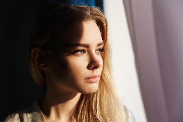 Sun shines over a face of beautiful woman standing before bright window Premium Photo