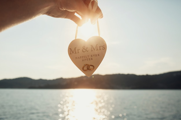 Sun shines over wooden heart with lettering 'mr & mrs happily ever after'  held before sea water Free Photo