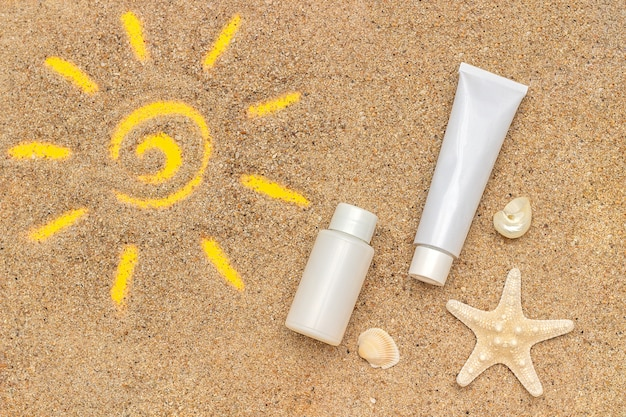 Sun sign drawn on sand, starfish and white tube, bottle of sunscreen. Premium Photo