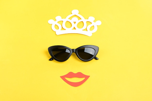 The sun with stylish black sunglasses, crown, smiling mouth on yellow flat lay Premium Photo