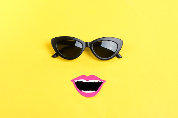 The sun with stylish black sunglasses, smiling mouth on yellow flat lay Premium Photo
