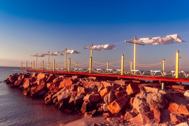 Sunbeds on the rocky pier by the sea Premium Photo