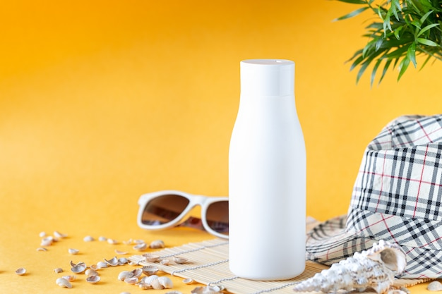 Suncare bottles, glasses, starfish palm leaves on a yellow background. beauty and care in the summer. copy space Premium Photo