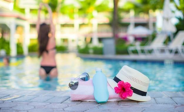 Suncream, hat, sunglasses, flower and tower near swimming pool Premium Photo