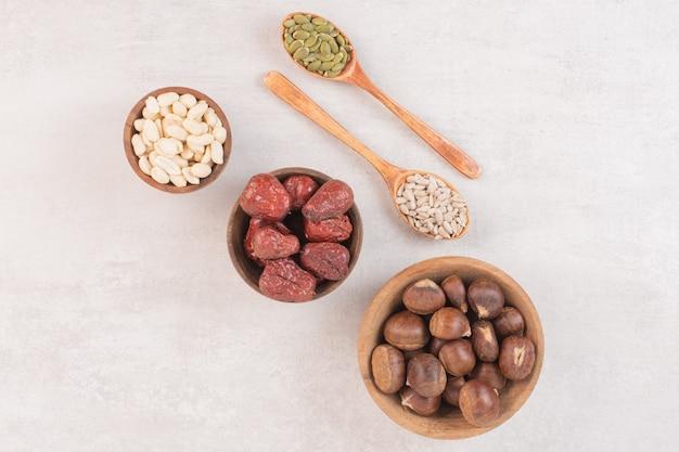 ひまわりとカボチャの種と白い表面のナッツのボウル。 無料写真